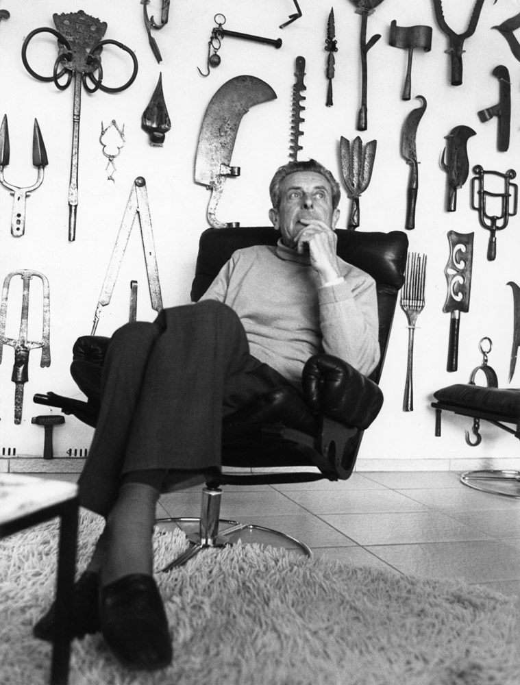 Louis Van Lint in his living room. Part of his tools collection covers the wall in the background.