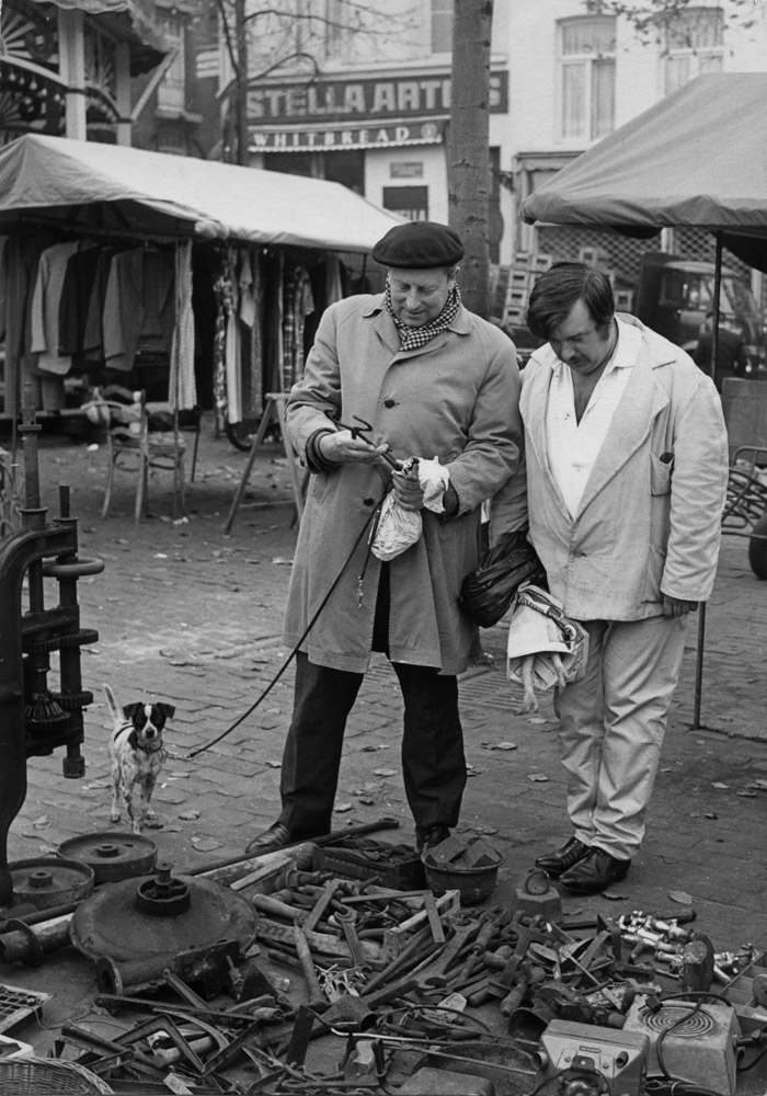 Louis Van Lint inspecting a old tool at an open market.